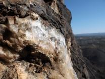 Debaixo da rocha chamuscada pelo fogo, heis que os cristais de quartzo reluzem.